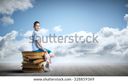 Adorable child sitting on pile of old books with bear toy in hand - stock photo