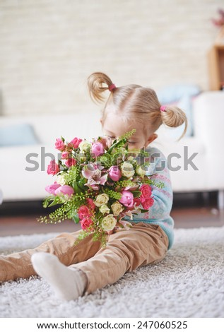 Adorable child smelling fresh flowers while sitting on the floor - stock photo