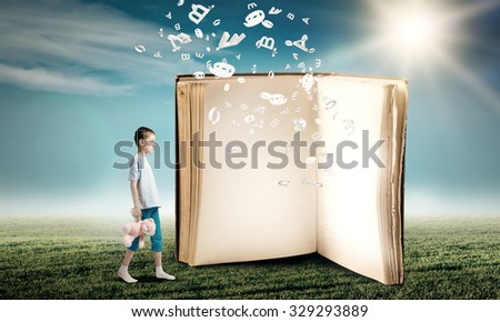 Adorable child standing with bear toy in hand and big old book - stock photo