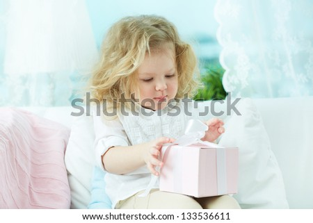 Adorable child unwrapping a birthday gift at home - stock photo