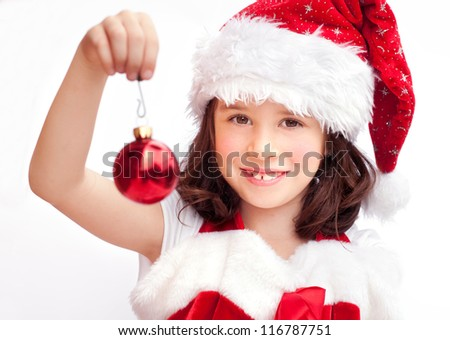 Adorable child wearing Santa Claus hat with a Christmas ball - stock photo