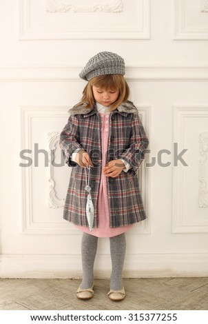 Adorable child wearing trendy coat , holding a Christmas ball. Indoor - stock photo