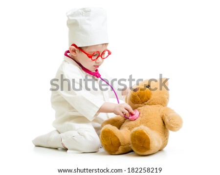 Adorable child with clothes of doctor playing with toy - stock photo