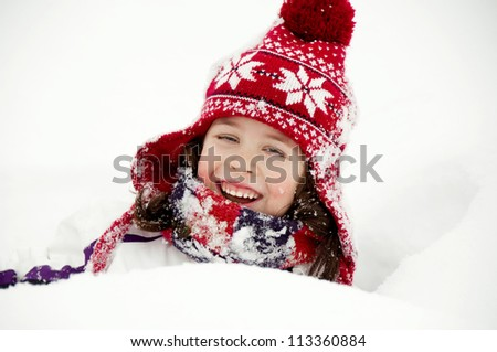 Adorable child with winter hat and scarf in snow