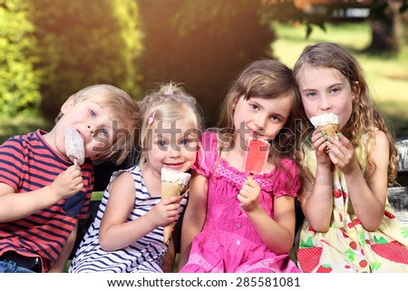 adorable children eating ice cream on holiday - stock photo