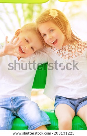 Adorable children having fun on swing outdoors, best friends playing on backyard in daycare, healthy and happy lifestyle, strong friendship concept  - stock photo