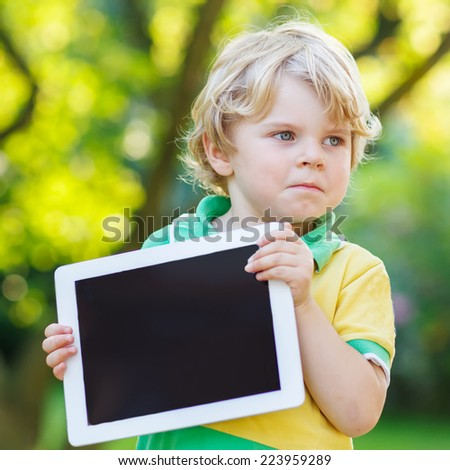 Adorable confused little kid boy holding tablet pc, outdoors. Preschool child learning with modern technology. - stock photo