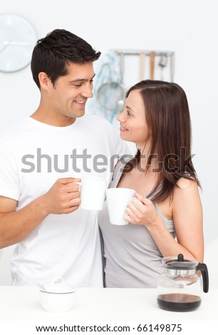 Adorable couple looking at each other while holding cups of coffee - stock photo