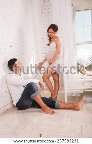 Adorable couple looking at the camera. Pregnant young woman - stock photo