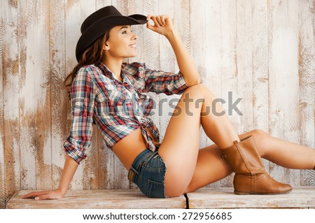 Adorable cowgirl. Beautiful young cowgirl adjusting her hat and smiling while sitting against the wooden background - stock photo