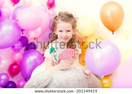 Adorable curly girl posing on balloons backdrop