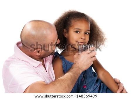 Adorable cute african child with afro hair wearing a denim dress. Her father is helping her to drink water from a clear glass.