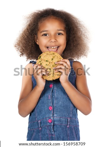 Adorable cute african child with afro hair wearing a denim dress. The girl is holding a big choc chip cookie. - stock photo