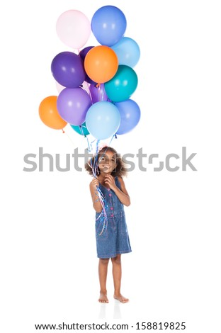 Adorable cute african child with afro hair wearing a denim dress. The girl is holding a bunch of bright coloured helium balloons. - stock photo