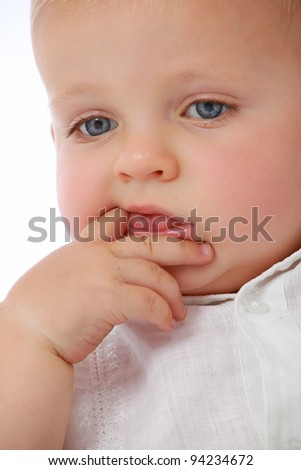 Adorable cute baby face looking down with fingers in mouth - stock photo