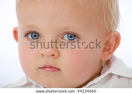 Adorable cute baby face looking with big blue eyes - stock photo