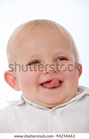 Adorable cute baby face pulling funny face and tongue out, laughing and smiling - stock photo