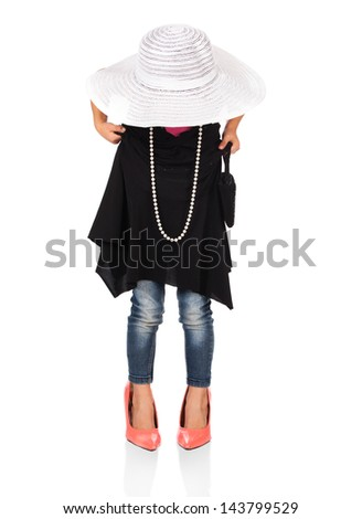 Adorable cute caucasian girl is playing dress up. She is wearing a black dress, white hat, earrings and coral high heel shoes. - stock photo