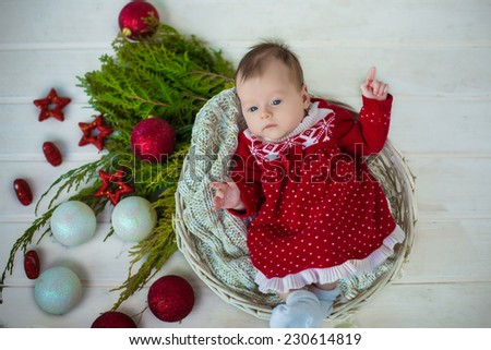 adorable cute christmas baby girl in red dress laying in basket on white floor background with green christmas tree leaves and white and red  decoration - stock photo