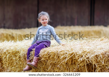 Adorable cute happy girl having fun with hay on a farm. Child enjoying autumn season and laughing. Happy childhood, lifestyle concept. - stock photo