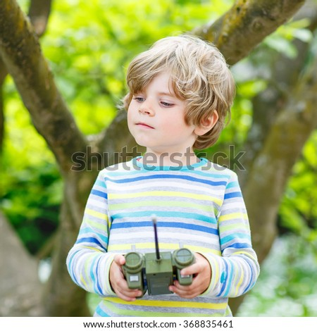 Adorable cute little child playing with toy on remote control, outdoors. Happy kid boy having fun on sunny summer day. Leisure, lifestyle for kids concept. - stock photo