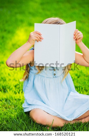Adorable cute little girl reading book in the garden, outside on grass - stock photo