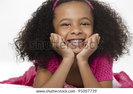 Adorable cute little girl with curly hair and big bright happy smiling expression - stock photo