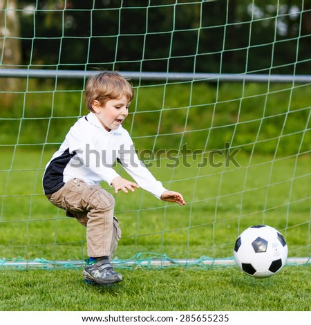 Adorable cute little kid boy playing soccer and football and having fun, outdoors on field. Active leisure with children on warm sunny summer day. - stock photo
