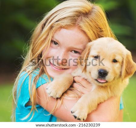 Adorable Cute Young Girl with Golden Retriever Puppy  - stock photo