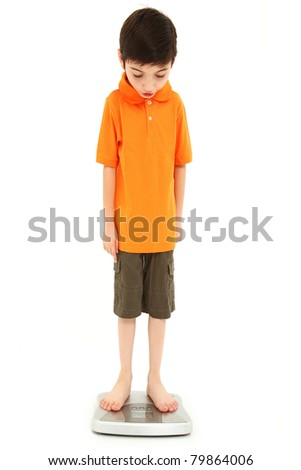Adorable eight year old boy on scale very thin anorexia nervosa childhood onset concept. - stock photo