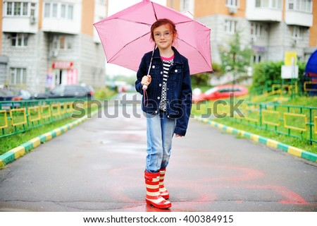 Adorable, elegant school aged kid  girl ,holding colorful umbrella walking in the city street in rainy day - stock photo