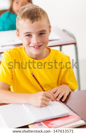 adorable elementary student in classroom writing classwork - stock photo