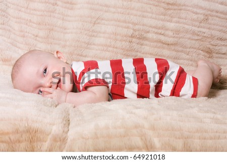 Adorable expressive happy baby boy from low perspective. - stock photo