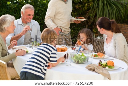 Adorable family eating in the garden - stock photo