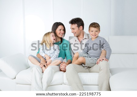 adorable family happily looking each other - stock photo