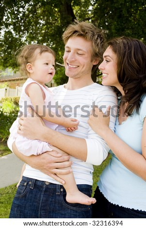 Adorable family outside of their home - stock photo
