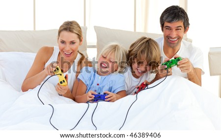 Adorable family playing video game lying on bed - stock photo