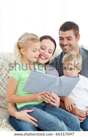 Adorable family reading a book together in the living-room at home