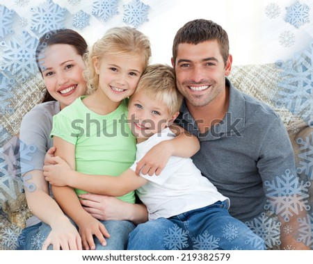 Adorable family sitting on the sofa and smiling against snowflake frame - stock photo
