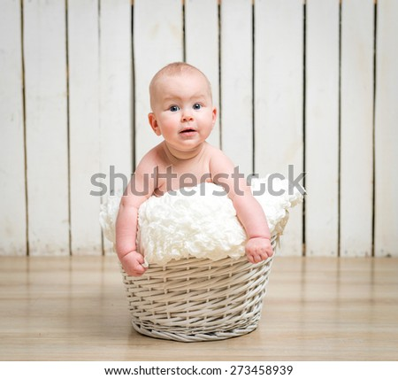 Adorable five month baby girl in wicker basket - stock photo