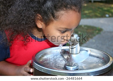 Adorable five year old African American Girl drinking from water fountain - stock photo