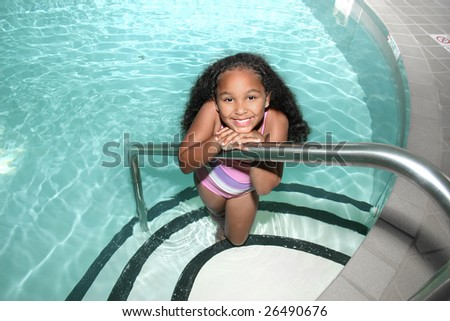 Adorable five year old African American Girl in indoor pool smiling. - stock photo