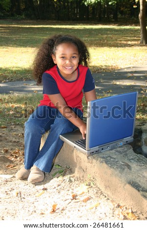 Adorable five year old African American Girl with laptop at park.