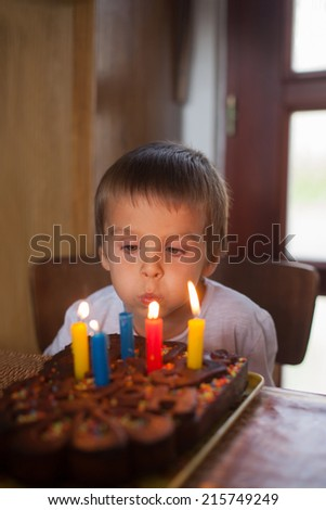 Adorable five year old boy celebrating his birthday and blowing - stock photo