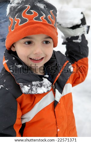 Adorable five year old getting ready to throw snowball. - stock photo