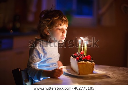 Adorable five year old kid boy celebrating his birthday and blowing candles on homemade baked cake, indoor. Birthday party for children.