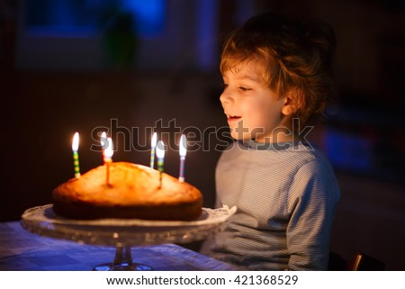 Adorable five year old kid boy celebrating his birthday and blowing candles on homemade baked cake, indoor. Birthday party for children. - stock photo