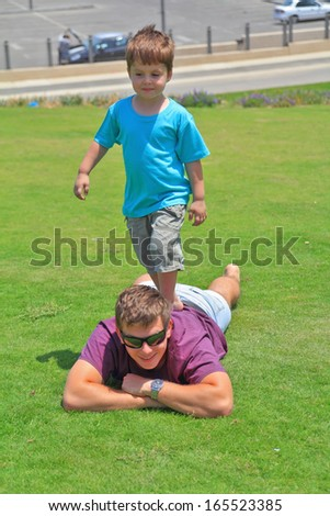 Adorable four year old boy having fun playing with his uncle on a green grass lawn - stock photo