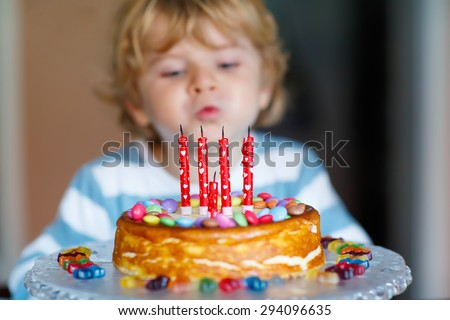 Adorable four year old kid celebrating his birthday and blowing candles on homemade baked cake, indoor. Birthday party for kids. Focus on cake - stock photo