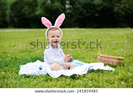 Adorable funny baby boy with bunny ears playing on green grass with Easter eggs - stock photo